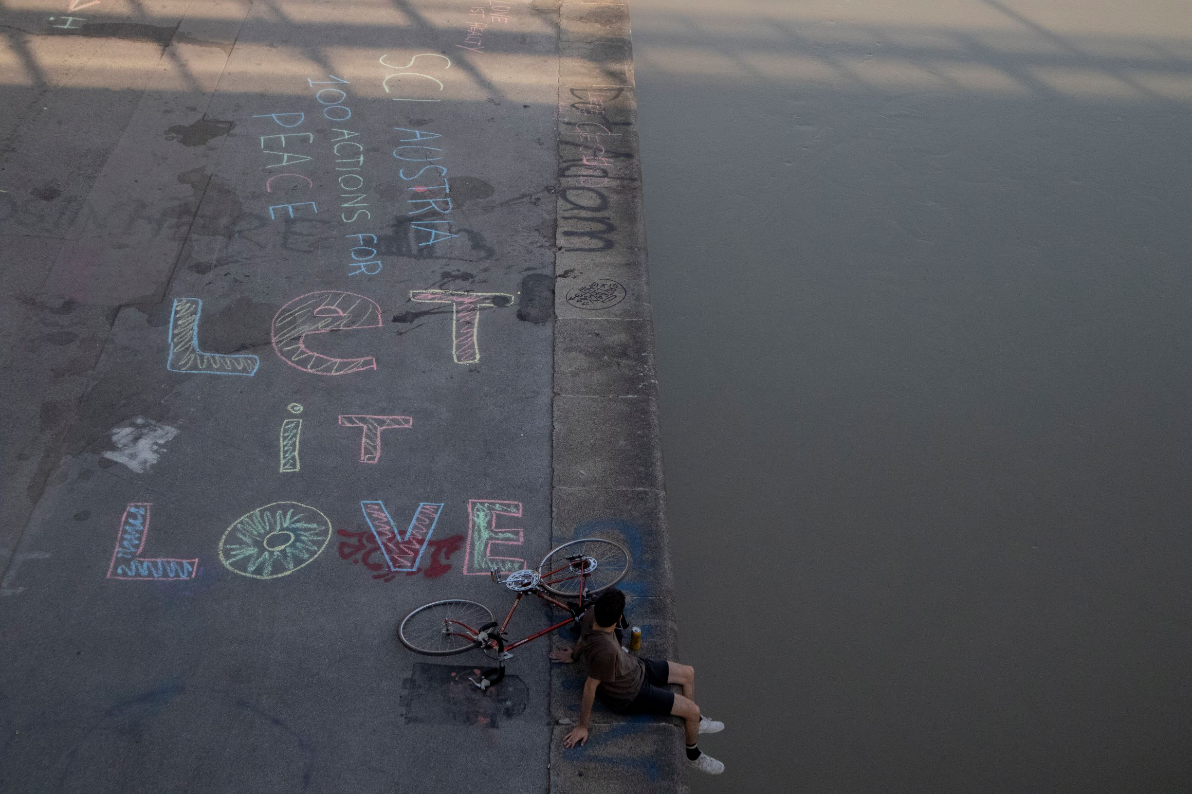 a man sitting by the river with a bike, on one half can be seen the river, in the other is the sidewalk with drawings